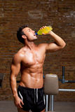 Muscle man at gym relaxed with energy drink Royalty Free Stock Photo