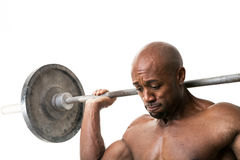 Muscle Man Holding Barbell. Toned and ripped lean muscle fitness man lifting weights isolated over a white background Royalty Free Stock Photo