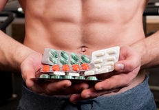 Muscle man holding blisters of pills Royalty Free Stock Images