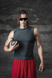 Muscle man is holding football ball. Muscle man is wearing sunglasses and holding football ball Royalty Free Stock Photo