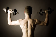 Muscle man  lifting dumbbells Royalty Free Stock Photo