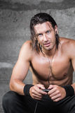 Muscle man listening to music. Handsome blue eyes muscle man listening to music and looking at camera stock image