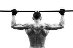 Muscle man making pull-up on horizontal bar against the sky.  Royalty Free Stock Photography
