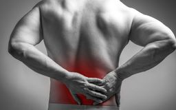 Muscle man with pain in his back. Red color zone is the pain. Medical concept on gray background stock photos