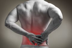 Muscle man with pain in his back. Red color zone is the pain. Medical concept on gray background stock images