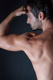 Muscle man posing on black background Royalty Free Stock Photography