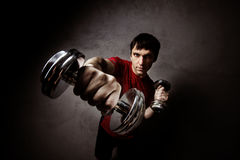 Muscle man posing with dumbbell s on wall backdrop Royalty Free Stock Image