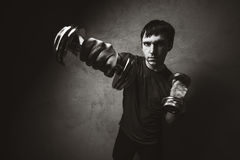 Muscle man posing with dumbbells on wall backdrop. Black and white photo Stock Image