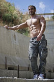 Muscle man shirtless outdoors, concrete wal Stock Photos