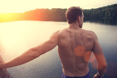 Muscle man standing on the cliff near the water outdoors and looking far away. Young and muscle man standing on the cliff near the water outdoors and looking far stock photography