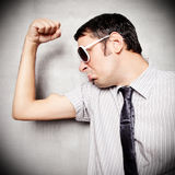 Muscle man. Young nerd showing his muscle Royalty Free Stock Photos