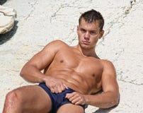 Muscle o homem despido 'sexy' molhado que encontra-se na rocha Foto de Stock