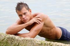 Muscle o homem 'sexy' despido molhado na água de mar Fotografia de Stock