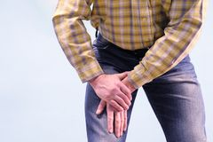 Muscle pain in the thigh. The man grabbed his thigh in a fit of pain. Suffers from diseases of joints and ligaments. The concept. Of health stock photo