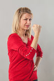 Muscle and power concept for frowning blond 20s woman Stock Photos