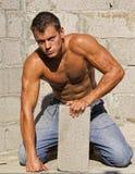Muscle reizvolle blanke schmutzige junge Arbeitskraft mit Block Stockfotos