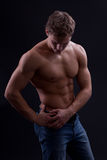 Muscle sexy naked young man posing in jeans Stock Image
