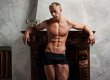 Muscle sexy young man posing near to a fireplace Stock Image
