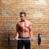 Muscle shaped body man with weights on brick wall Stock Photo