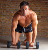Muscle shaped man on knees with training weights. On brickwall Royalty Free Stock Photo