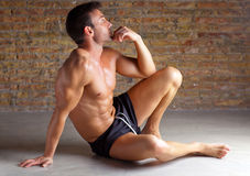 Muscle shaped man sitting relaxed on brickwall Stock Photo