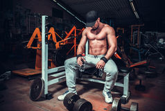 Muscle shaped man tired sitting relaxed. With weights and energy drink royalty free stock photos