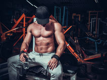 Muscle shaped man tired sitting relaxed. With weights and energy drink stock image