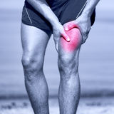Muscle sports injury of male runner thigh. Running muscle strain injury in thigh. Closeup of runner touching leg in muscle pain Royalty Free Stock Photos