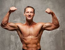 Muscle sportsman on a grey background Royalty Free Stock Image