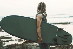 Muscle surfer holding surfboard, looking the ocean. Young athletic surfer with long dreadlocks and tattoo near the ocean with his surfboard in Indonesia, Bali Stock Photography