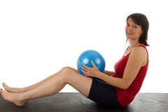 Muscle training. A young woman with a small stability ball royalty free stock photos