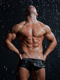 Muscle wet sexy naked man posing under the rain Royalty Free Stock Photo