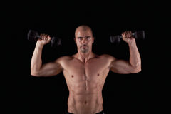Muscle young man with dumbells Royalty Free Stock Image