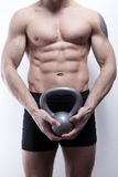 Muscle young man with kettlebells royalty free stock images