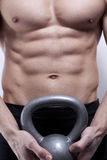Muscle young man with kettlebells. Muscle males's body in gym with kettlebells stock photography