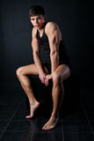 Muscle young man sits on a black cube Royalty Free Stock Photography