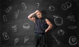 Muscled молодой человек обдумывая на чем выбрать: старье или здоровая еда стоковое фото rf