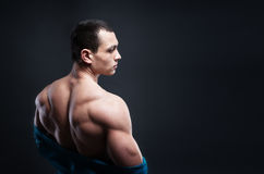 Muscled male model showing his back. Bodybuilder showing his back and biceps muscles, personal fitness trainer. Strong man flexing his muscles Stock Photography