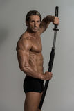 Muscled Male Model In Studio With A Sword Royalty Free Stock Photography