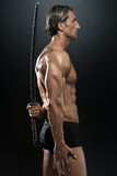 Muscled Male Model In Studio With A Sword Royalty Free Stock Photos