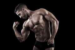Muscled man on a black background Stock Images