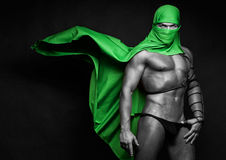 Muscled man with cloak. A muscular male model with a green cloak stock photo