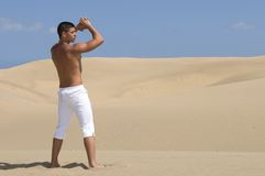 Muscled man in the desert dunes with white trouser Royalty Free Stock Images