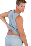 Muscled man grimacing because of a back pain Royalty Free Stock Photography