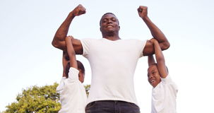 Muscled man holding his children stock footage
