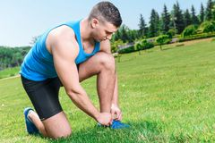 Muscled sportsman during training. Portrait of a young handsome muscular sportsman sitting and tying shoelaces on his blue running sneakers, wearing black blue Royalty Free Stock Images