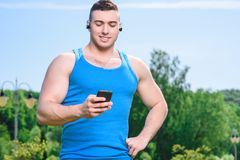 Muscled sportsman during training. Portrait of a young handsome muscular sportsman standing reading messages on his smartphone and smiling, wearing black blue Royalty Free Stock Photos