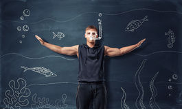 Muscled young man with drawn swimming mask and snorkel standing on the backround of cartoon underwater world Royalty Free Stock Photos