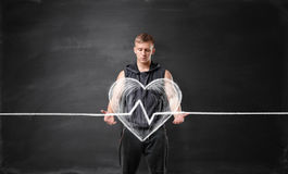 Muscled young man holding big drawn beating heart on the background of a blackboard Stock Images