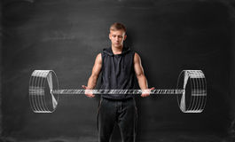 Muscled young man lifting hand drawn weight on the background of blackboard Royalty Free Stock Photography